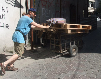 Sen with 3 wooden crates using a wagon lent to us approaches Taksim Square.