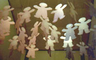 First Lessons  in Relativity, installation of up to 50 hanging cardboard dolls in shades of pink to blue,  1992.